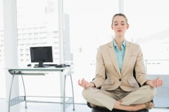 Concentrated calm businesswoman sitting in lotus position on her swivel chair with eyes closed