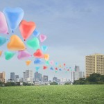 Colorful heart love balloon float on air at city background
