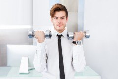 Businessman Exercising With Dumbbells At Office